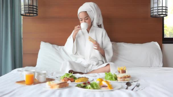 footage of beautiful asian woman having breakfast in bed at hotel