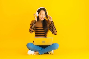 Beautiful portrait young asian woman sit on the floor with laptop and headphone on yellow isolated background