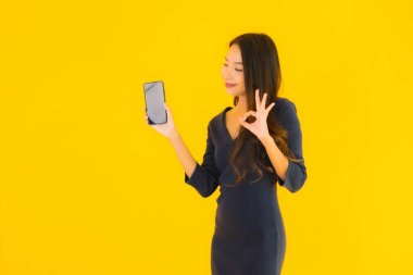 Portrait beautiful young asian woman with smart mobile phone or cellphone on yellow isolated background