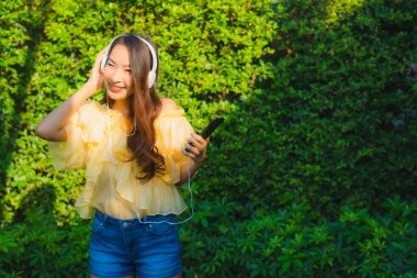 Young asian woman using smart mobile phone with headphone for listen music around outdoor garden nature view