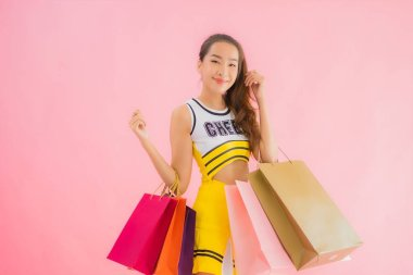 Portrait beautiful young asian woman cheerleader with shopping bag on pink isolated background