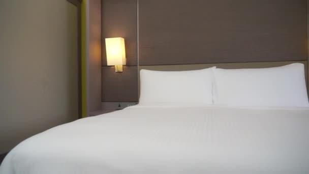 interiér hotelového pokoje s bílou postelí a dvojitou expoziční lampou