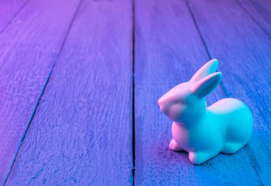 White Easter bunny on a blue wooden background