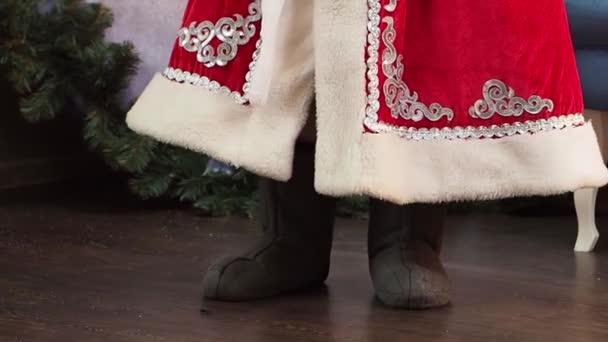 Danses de père Frost. Bottes de feutre se bouchent. Le personnage de Noël et du nouvel an de conte de fées se déplace rythmique. On voit le fond de ses vêtements et de chaussures.