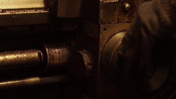 Munka folyamat: a gép műszaki üzem. A férfi gépkezelő szabályozza működő folyamat, egy szabályozókar fordult. A részletek élesítette. Fém borotválkozás legyek. Alulnézet fel.