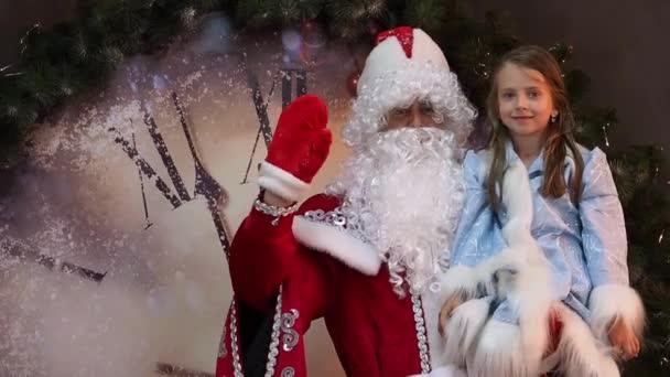 Radostné dítě a Mrazík úvodní ruku vlny. Silvestr pro děti vánoční dovolenou. Nový rok postavy na pozadí obrovských hodin