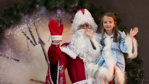 A szép lány Snegurochka, és apja fagy Mikulás hullám a kezét. Előestéjén a gyermekek karácsonyi ünnep. A háttérben hatalmas óra a New Years karakterek.