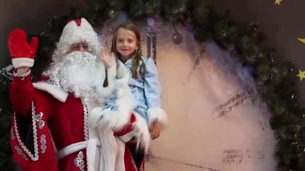 Az örömteli gyermek és fagy apa szívesen kézzel hullámok. Előestéjén a gyermekek karácsonyi ünnep. A háttérben hatalmas óra a New Years karakterek.