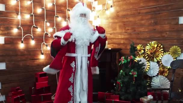 Father Frost Santa Claus dances against the background of a bright garland. The Christmas childrens character fierily and beautifully dances.