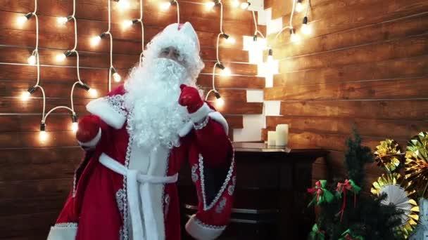 Otec Frost Santa Claus tance na pozadí světlé věnec. Děti Novogodniyrozhdestvensky charakter fierily a krásně tančí.