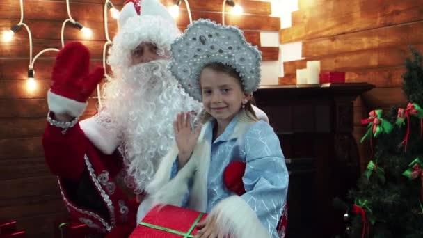 Otec Frost Santa Claus a Sněguročka mávnout rukou a úsměv. Nový rok vánoční pohádky znaky v domě na krb radostně Vítejte v prohlížeči