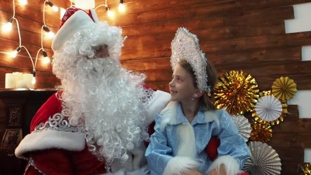 Otec Frost Santa Claus řekne něco malé holčičce Snegurochka. Nový rok vánoční pohádky znaky komunikovat posezení u krbu