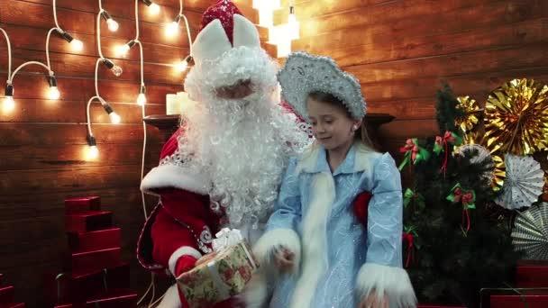 Otec Frost Santa Claus dává malé holčičce Snegurochka dárek v krabičce. Novoroční pohádka vánoční postavy ruské tradice v domě na krb