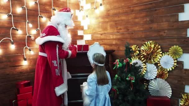 Malá holčička Snegurochka představuje otce Frost Santa Claus dárkové krabičky. Nový rok vánoční postavy ruských tradic vyměňují dárky v domě na krb