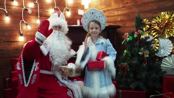 DED Mroz Santa Claus a malá holčička Snegurochka drží boxy s dárky. Nový rok vánoční pohádky znaky v domě na krb s úsměvy Vítejte v prohlížeči