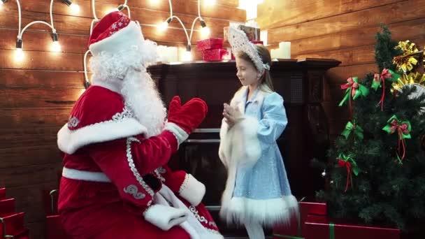 Otec Frost Santa Claus a malá holčička Snegurochka hrát dlaně. Nový rok vánoční pohádkových postav ruské tradice hry pat--dort na krb a jedle
