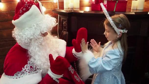 Otec Frost Santa Claus a malá holčička Snegurochka hrát dlaně. Nový rok vánoční pohádkových postav ruské tradice hry pat--dort na krb a jedle. Detailní záběr