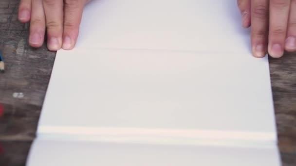 Žena dává list papíru na polovinu a odtržení od základu. Kreativní práci s papírem. Nůžkové list papíru. Zblízka. Retro styl.