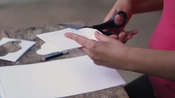 Žena se vyřízne mrak z papíru. Kreativní práci s papírem. Boční pohled. Zblízka. Retro styl