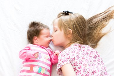 little girl kissing nose her little sister and lying on bed