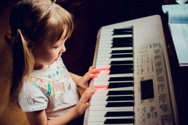 Little girl playing a synthesizer