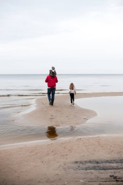 father with little daughters wearing warm clothes and walking on sandy seashore