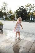aranyos kislány szórakozik játék közben a pocsolya az utcán