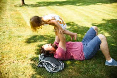 father with little daughter having fun while playing on green grass at summer park