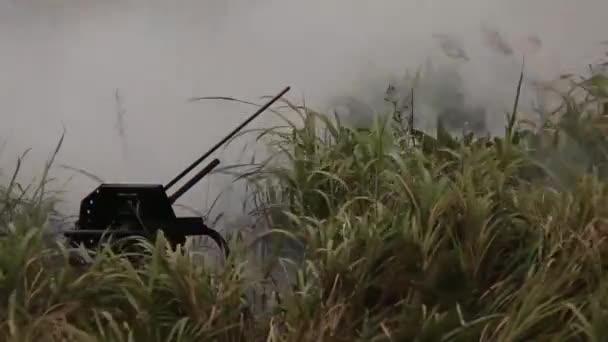 Das Abfeuern von Militärwaffen auf einem Feld mit hohem Gras