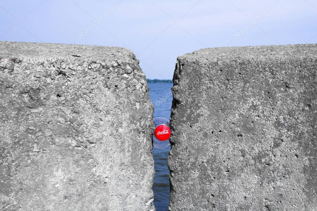 Kyiv, Ukraine - September 1, 2018: Coca Cola between two rocks against the background of a river