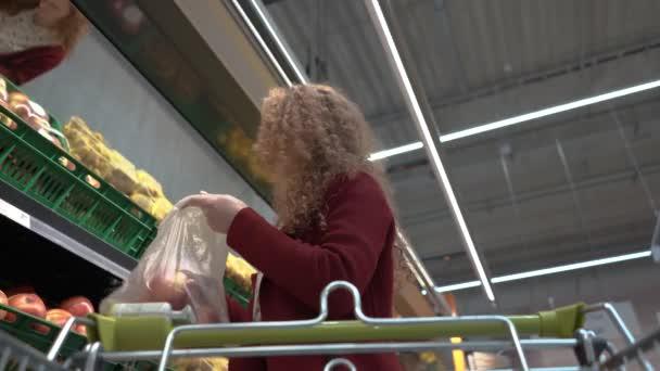 Mladá krásná žena zvolí jablka v supermarketu