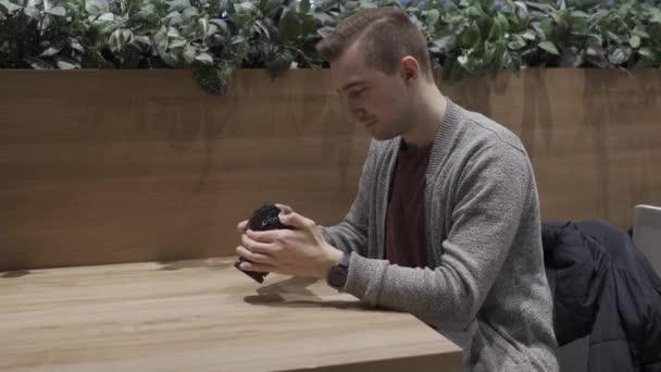 mladý atraktivní muž fotografování na kameru, zatímco sedí u stolu v kavárně