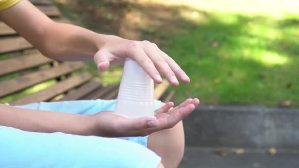 A teenager breaks a white plastic cup with both hands