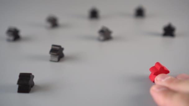 Ruka nastavuje červenou postavu obklopenou černými postavami na šedém povrchu. Koncepce vedoucího týmu