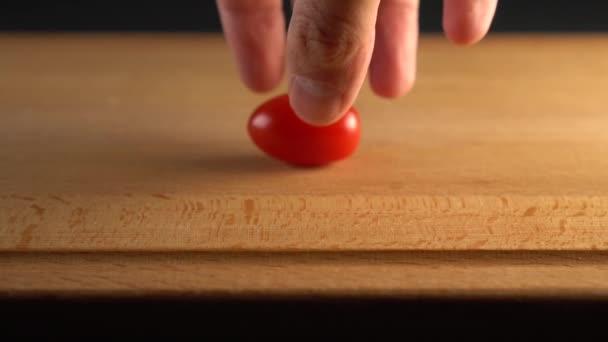 Hand pflückt reife Kirschtomaten von einer Holzoberfläche. auf schwarzem Hintergrund. Zeitlupe. Kochen pflanzliche Ernährung Mahlzeiten