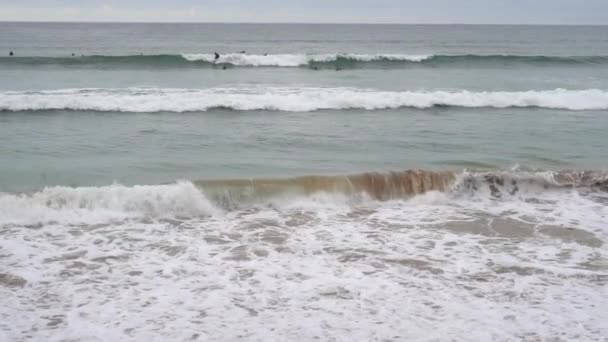 Evening ocean surf. Foamy waves fill the sandy beach. Surfers straddled the wave. A large group is waiting