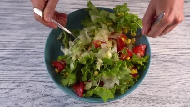 Žena má dvě vidličky zeleninový salát s rajčaty, bylinkami a kukuřicí v akvamarínovou destičce. Na dřevěném pomalované bílém stolku.