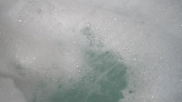 A stream of water from the shower blurs a bunch of foam into the bathtub. Bubbles form and fall. Use of hygiene products