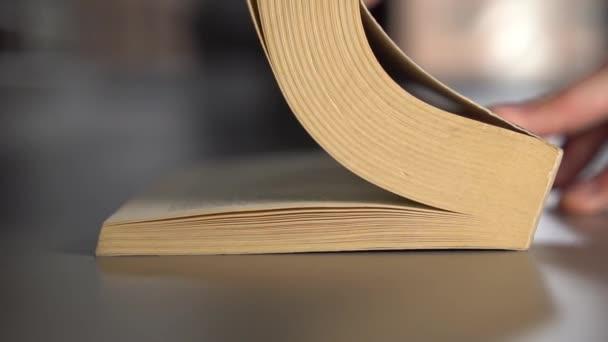 Muž listí starou knihou, obracejí se přes stránky na šedém povrchu. Zpomaleně. Koncepce znalostí