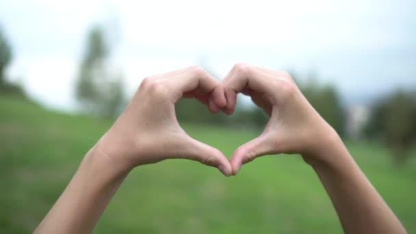 A tinédzser hajtogatott kezét az alakja a szív a háttérben a zöld fák és az ég a parkban