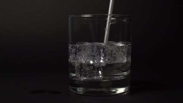 Někdo pije uhličitanovou minerální vodu se stříbrnou slámou. Prázdné sklo s čerstvým nápojem na černém pozadí close-up