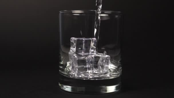 Nalévání uhličitanové minerální vody do sklenice s kostkami ledu na černém pozadí zblízka se stříkanci a kapkami. Zpomalený pohyb