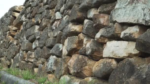 Zničená opěrná zeď z přírodního hnědého kamene podél silnice s ohraničením proti obloze