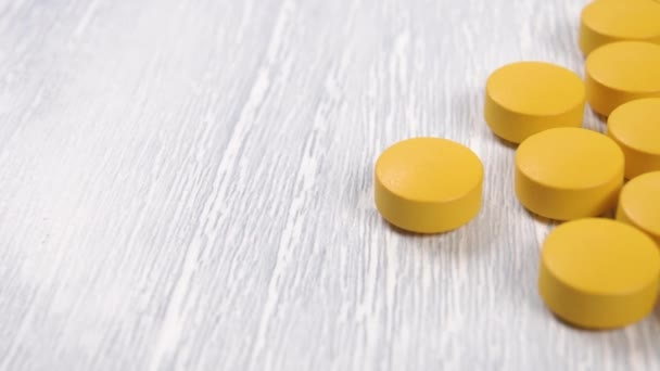 Yellow tablets with vitamin C on a wooden surface close-up. A handful of drugs to improve immunity to fight coronavirus. Macro