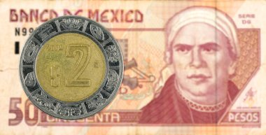 2 mexigan peso coin against 50 mexican peso bank note