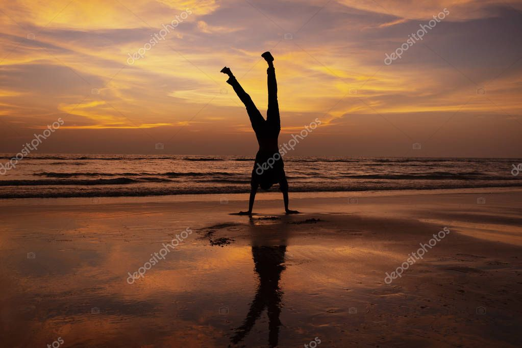 Man does handstand on beach at sunset