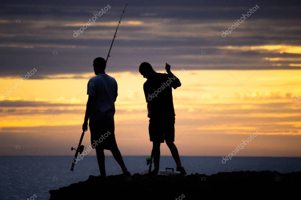 silhouette of two guys fishing on the beach at sunset