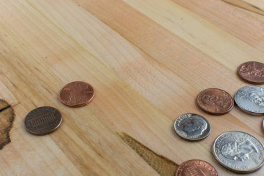 US currency pocket change placed on a wooden table.