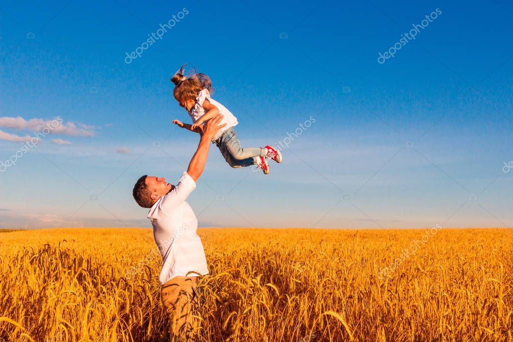 Happy family - the father throws his daughter in the middle of a wheat field on a sunny summer day. Concept of freedom