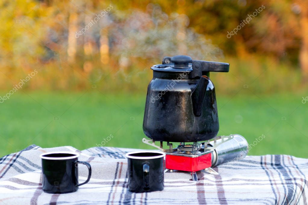 Marching hot iron black smoking kettle on red gas burner and iron mugs are standing on the table on white checkered tablecloth against the background of the autumn forest. Concept family recreation